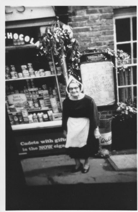 A historical photo of a shop keeper standing outside of her shop