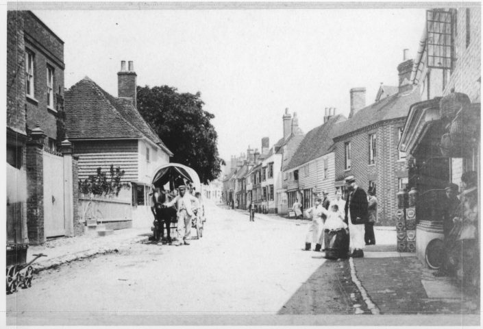 A historical photo of the High Street, including horse and cart