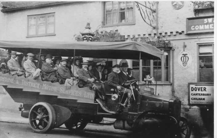 A historical photo of a bus full of people