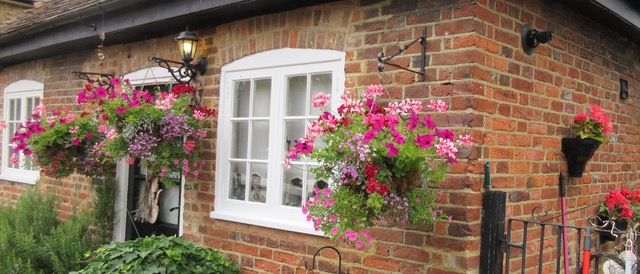 Cottage displaying floral hanging baskets