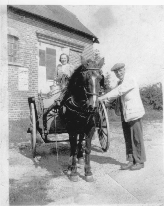 A historical photo of a lady and man with a horse and cart