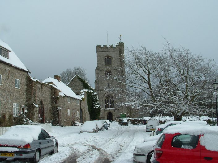Local church and cars covered in snow.