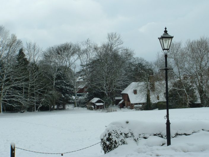 Beautiful farm house, trees and grounds covered in snow.