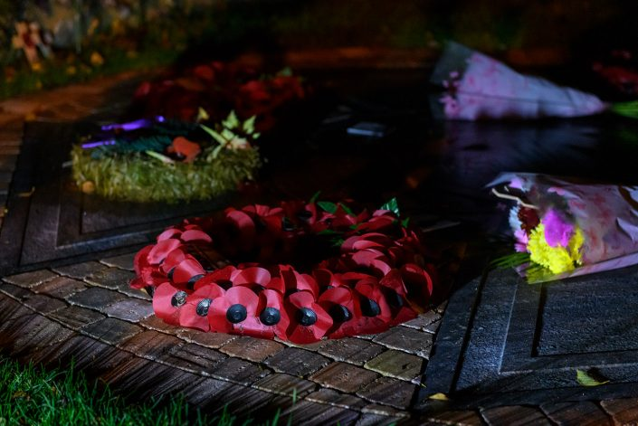 Artificial poppy wreaths of remembrance and a bunch of flowers