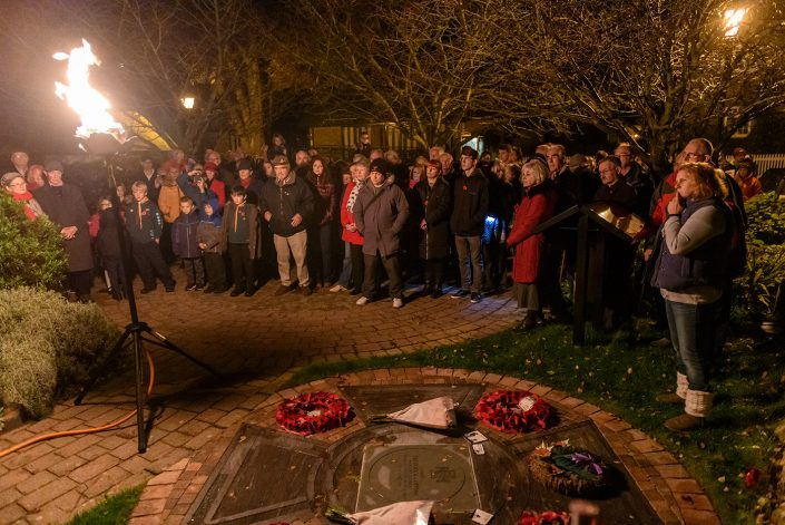 Group of local people at night with a large firelight as a torch, there are some read poppy wreaths. It looks like a remembrance ceremony.